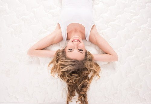 A woman, laying on her back, on a pristine mattress, smiling at the camera.