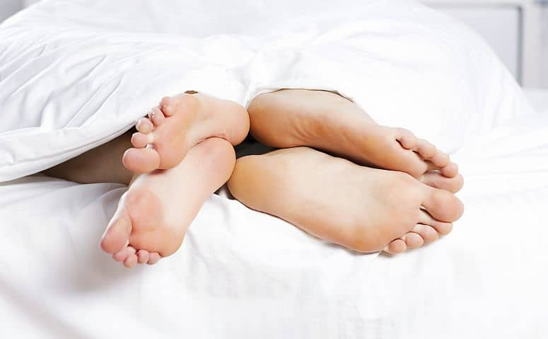 Couple in bed, comfortably asleep.
